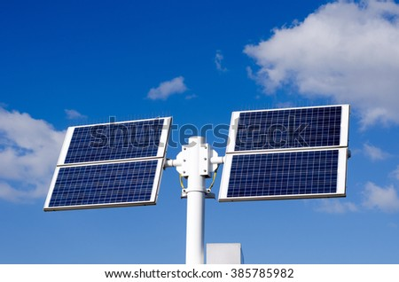solar panels over blue and white sky