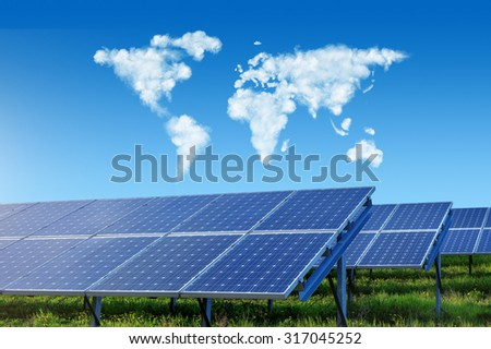 solar panels under blue sky with world map made of clouds - stock photo