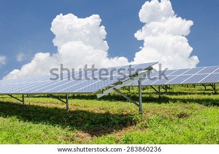 Solar panels with green field in bright sky day - stock photo