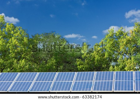 Solar panels with trees and blue sky - stock photo
