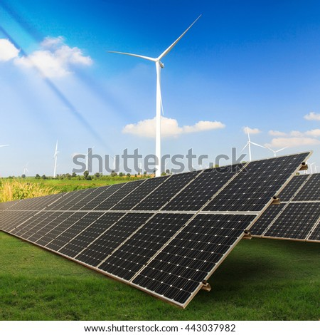 Solar panels with wind turbine on green field  - stock photo