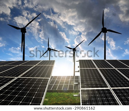 Solar panels with wind turbines in the setting sun