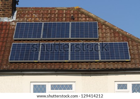 Solar photovoltaic panel array mounted on a tiled house roof against a blue sky