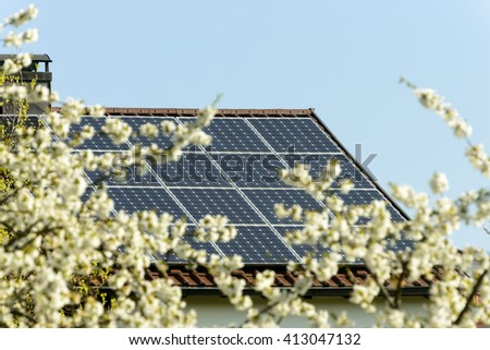 solar photovoltaic panels on a roof in springtime with blurred blossoming cherry flowers in foreground,  shot in Stuttgart, Germany
