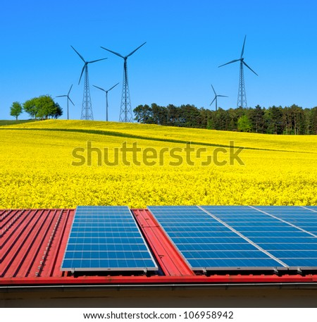 Solar power cells on a barn roof with a view over rapeseed field with windmills on the horizon - stock photo