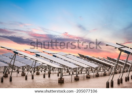 solar power farm in  sunset , develops coastal tidal flats and green energy - stock photo