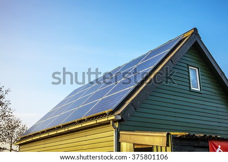 Solar power generation technology on house roof, alternative energy and environment protection ecology. - stock photo