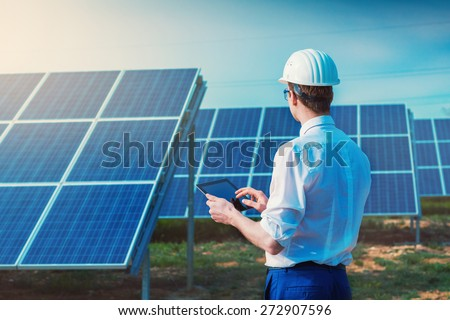 Solar power plant. Engineer with tablet computer on a background of photovoltaic panels. Science solar energy. - stock photo
