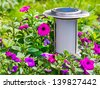 Solar-powered garden lamp on flower background. - stock photo