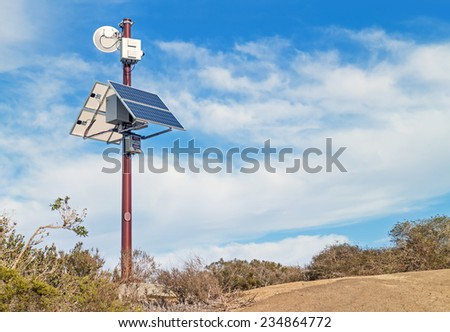 Solar powered surveillance camera monitoring rural area. Video camera mounted on metal pole above solar panels. Blue sky and clouds background.  - stock photo