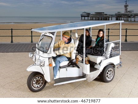 Solar powered tuc tuc at the beach, picking up two young women - stock photo