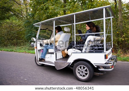 Solar powered tuc tuc with two passengers on the road