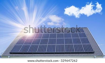 Solar roof on a house reflects the sun - stock photo