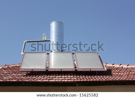 Solar water heating panel on a house roof - stock photo