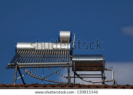 Solar water heating system on a house roof - stock photo