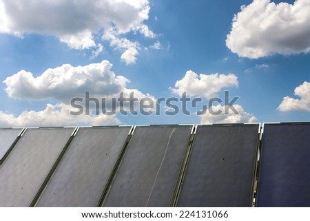 Solar water heating system on the red roof with blue sky and clouds - stock photo