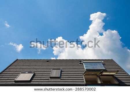Solar water panel with dormers on a roof against blue sky - stock photo