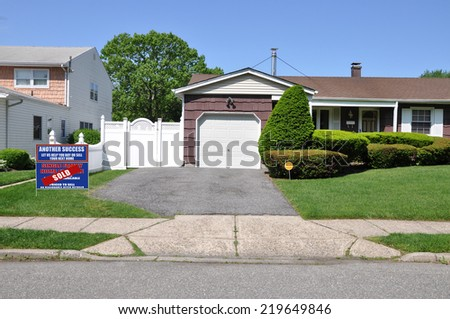 Sold (another success let us help you buy sell your next home) real estate sign driveway entrance suburban home residential neighborhood USA clear blue sky - stock photo