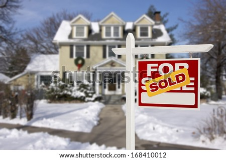 Sold Home For Sale Real Estate Sign in Front of Beautiful New House in the Snow. - stock photo