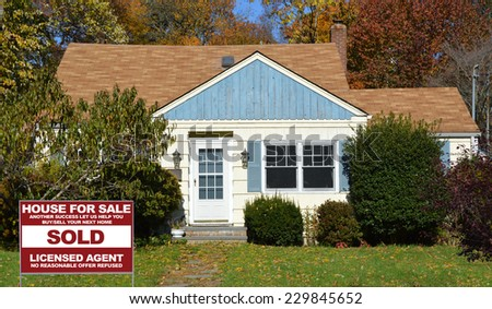 Sold Real Estate (another success let us help you buy sell your next home) sign on front yard lawn of suburban house residential neighborhood USA fall season - stock photo