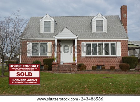 Sold Real Estate (another success let us help you buy sell your next home) sign Suburban brick cape cod style home overcast sky residential neighborhood USA - stock photo