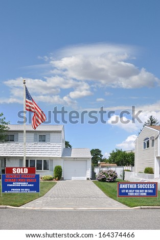 Sold Real Estate Sign American Flag Pole Suburban Home Driveway Street Curb Residential Neighborhood USA Blue Sky Clouds - stock photo