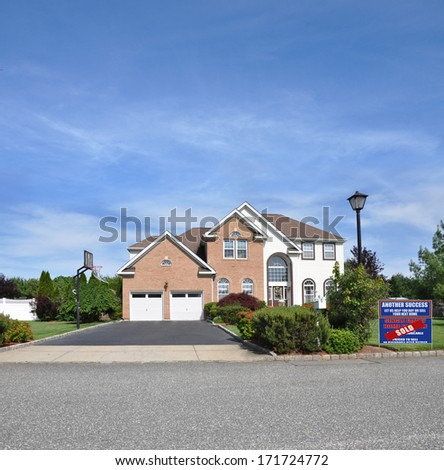 Sold Real Estate Sign 'another success let us help you buy sell you next home' Suburban McMansion style brick home Landscaped sunny residential neighborhood USA blue sky clouds - stock photo