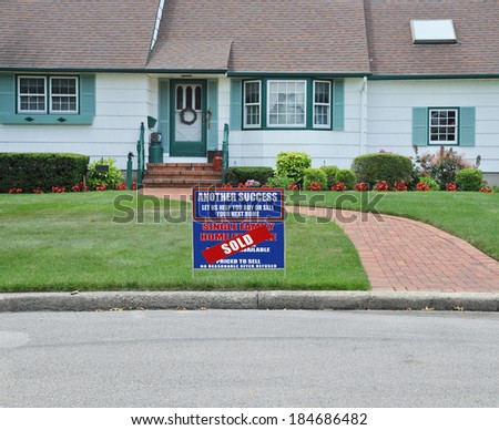 Sold Real Estate sign (another success let us help you buy sell your next home) Close Up of Suburban Home House Front Landscaped Brick Walkway Curb Residential neighborhood USA