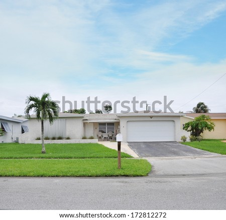 Sold Real Estate Sign 'Another Success let us help you buy sell your next home' Suburban Ranch Style Two Car Garage Landscaped Home residential neighborhood blue sky clouds USA - stock photo