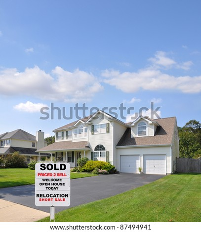 Sold Real Estate Sign on Front Yard Lawn of Landscaped Suburban Home in Residential Neighborhood Sunny Blue Sky Day - stock photo