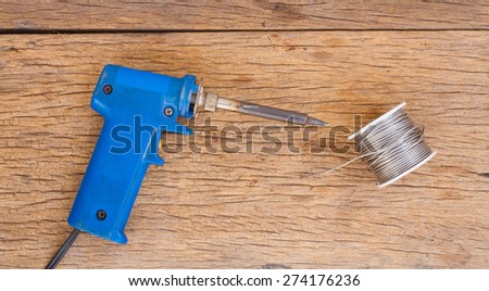 Solder and lead on wooden background - stock photo