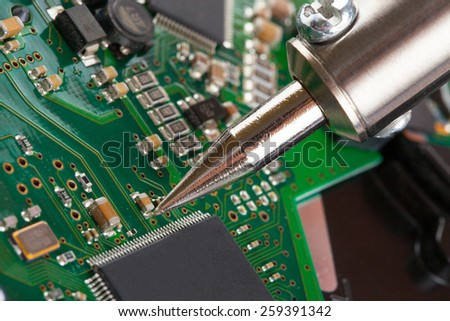 Soldering iron and microcircuit - closeup studio shot - stock photo