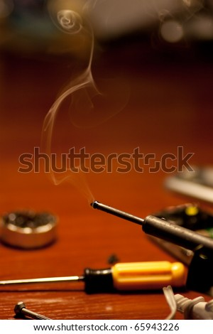 Soldering iron and smoke close up - stock photo