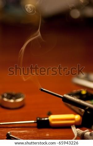 Soldering iron and smoke close up - stock photo