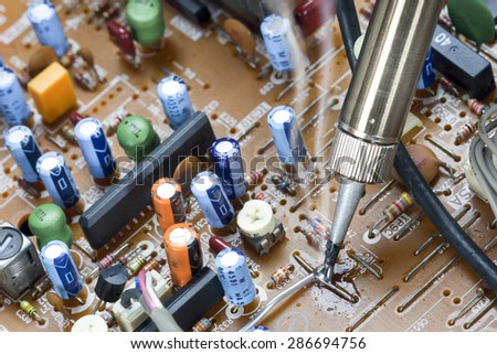 Soldering iron and verification testing of electronic circuits - stock photo