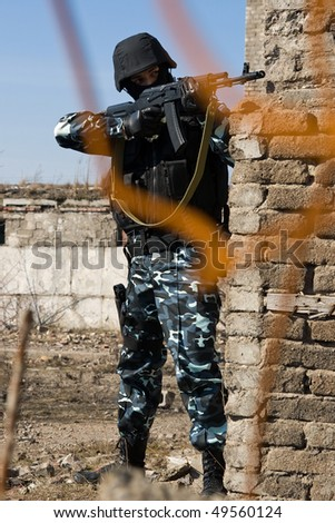 Soldier aiming target with automatic russian AK-47 rifle - stock photo