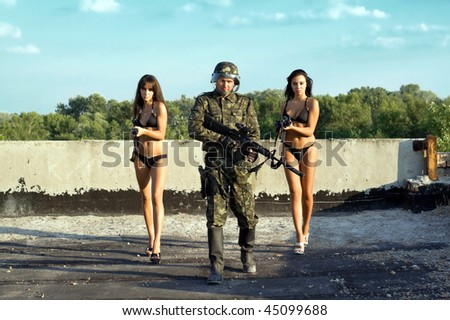Soldier and two women in underclothes with rifles - stock photo
