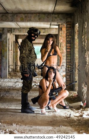 Soldier and two women smoking in the abandoned building - stock photo