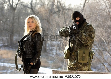 Soldier and young blonde armed with rifles - stock photo