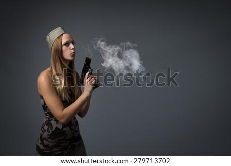soldier blowing on gun, dark background - stock photo