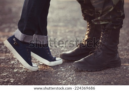 Soldier boots saying goodbye his girlfriend in jeans - stock photo