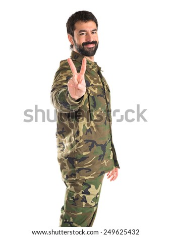 Soldier doing victory gesture  - stock photo