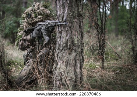 Soldier dressed in ghillie suit, aiming with assault rifle, hidden behind tree - front view