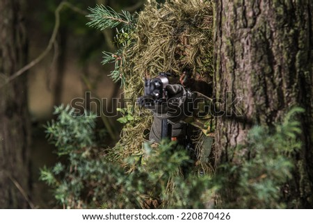 Soldier dressed in ghillie suit, aiming with machine gun, hidden behind tree - stock photo
