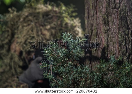 Soldier dressed in ghillie suit, aiming with machine gun, hidden behind tree, focus on barrel - stock photo
