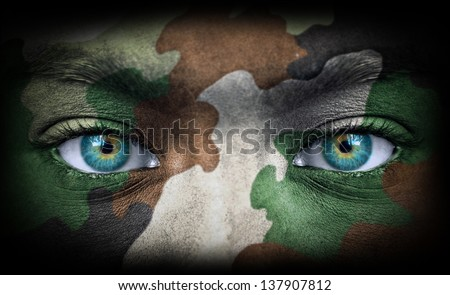 Soldier face with army colors looking from dark - stock photo