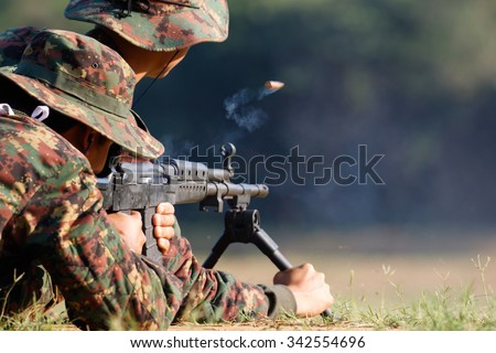 Soldier firing rifle gun to target with bullet cartridge in the air