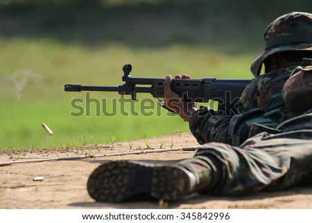 Soldier firing rifle gun to target with bullet cartridge in the air - stock photo