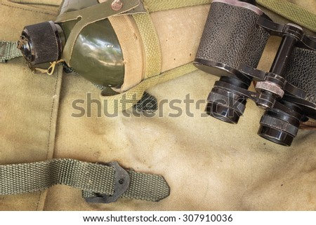 Soldier flask (canteen) in decay cloth winding and classic binoculars on rucksack - stock photo