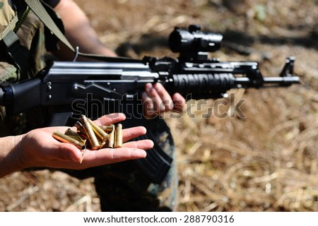 soldier holding a gun and bushings at hand - stock photo